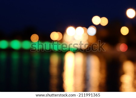 Blurred street lights and reflection in water background. Nightlife wallpaper, a lot of copyspace - stock photo