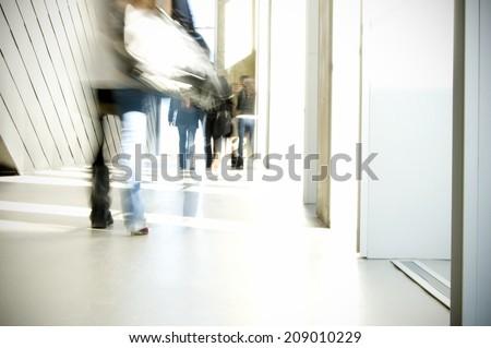 Blurred students walking in school hallway - stock photo