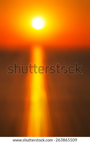 Blurred sun and its reflection in the sea at sunset. abstract composition - stock photo