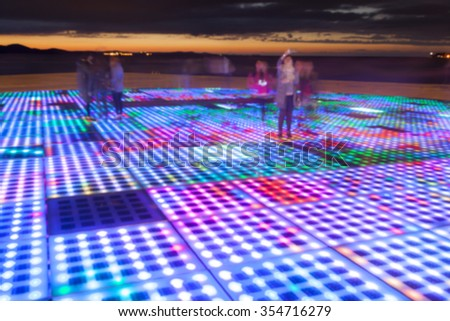 Blurred sun sculpture panel lighting up at night. - stock photo