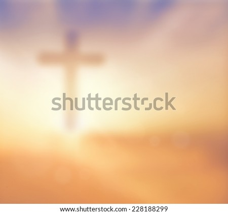 Blurred the cross on a sunset. - stock photo