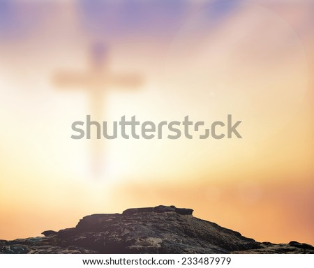 Blurred the cross on blurred sunset background. - stock photo