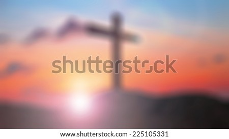 Blurred the cross on the mountain golgotha representing the day of christs crucifixion in a sunset. - stock photo