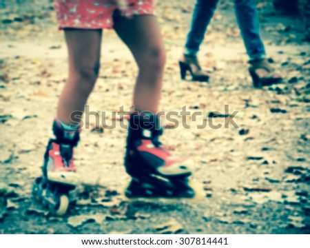 Blurred toned photo of teenager's legs with roller blades in motion and female legs at background. Luxembourg park (Paris,France) with fallen leaves on the ground.  - stock photo