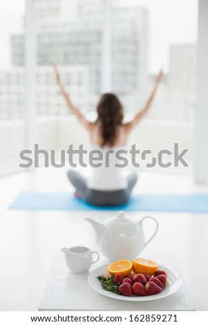 Blurred toned young woman sitting in meditation posture with healthy food in foreground at fitness studio - stock photo