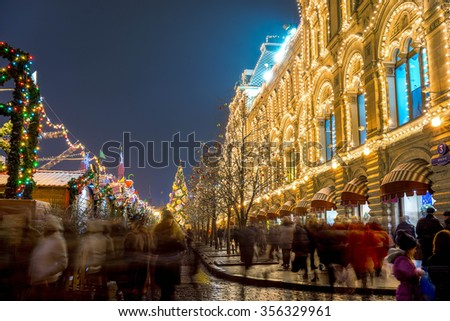 blurred tourists near illuminated facade of GUM Department store on Red Square during Christmas Fair in Moscow. Red Square is the central historical square in Moscow.  - stock photo