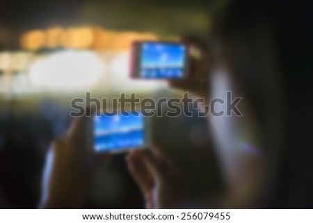 Blurred travel backgrounds of smartphone user on night time.