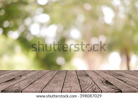 blurred tree plant forest in autumn season with wooden panel tiles plank backdrop:blurry of green sunshine backgrounds with bokeh lens flares lights:natural wallpaper with sun concept:spring season. - stock photo