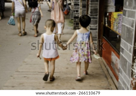 Blurred two childrens walk together in chinese town - stock photo