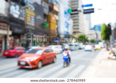 Blurred unfocused city view at day time. Unfocused cars in the way. Unfocused red car.