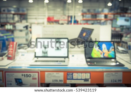 Blurred variety of laptops and notebooks on display at computer department in distribution warehouse or storehouse. Defocused background of technology inventory, hypermarket, wholesale bokeh light.