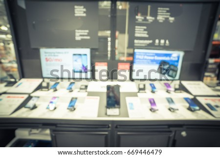 Blurred variety of modern smart phones on display at cell phone department in distribution warehouse or storehouse. Defocused background of technology inventory, hypermarket, wholesale. Vintage tone.