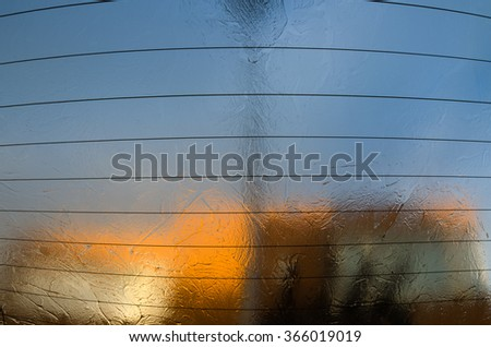 Blurred view from frozen car rear window. Warm colors of the rising sun reflections through ice and warming wires on the window. - stock photo