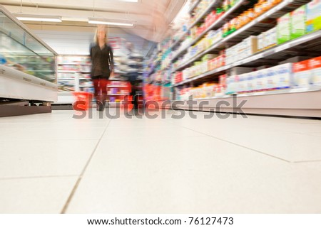 Blurred view of people in supermarket while shopping - stock photo