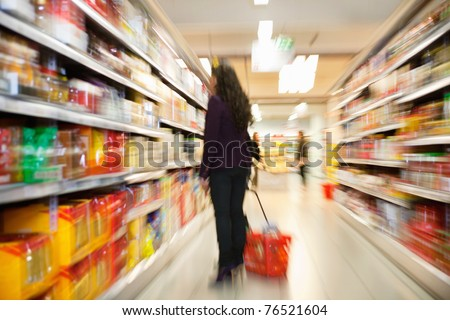 Blurred view of woman looking at products with people in the background in shopping centre - stock photo