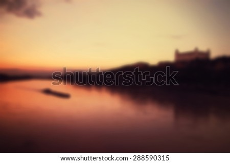 Blurred vintage background of sunset on the Danube River with Bratislava Castle View in Bratislava, Slovakia - stock photo