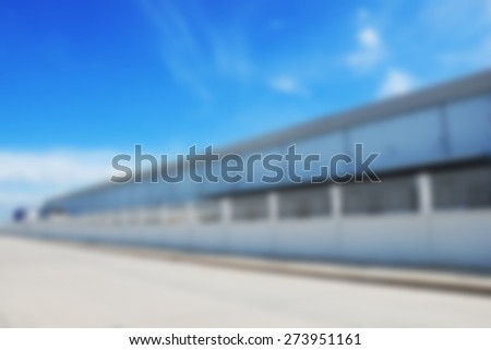Blurred warehouse building with beautiful blue sky - stock photo