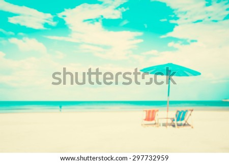 Blurred white sand beach with beach chairs and parasol - summer holiday and vacation background concepts