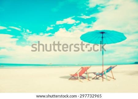 Blurred white sand beach with beach chairs and parasol - summer holiday and vacation background concepts - stock photo