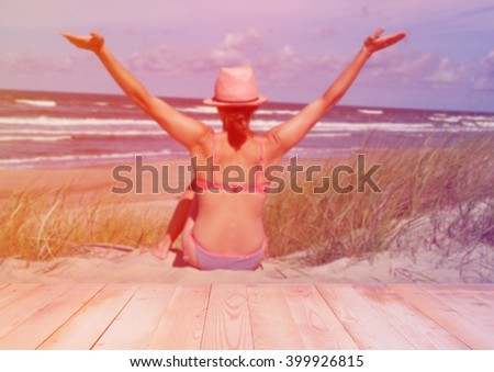 Blurred woman at the beach with wooden background - stock photo