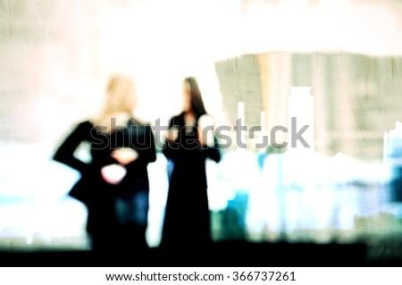 Blurred women walking in a shopping center - stock photo