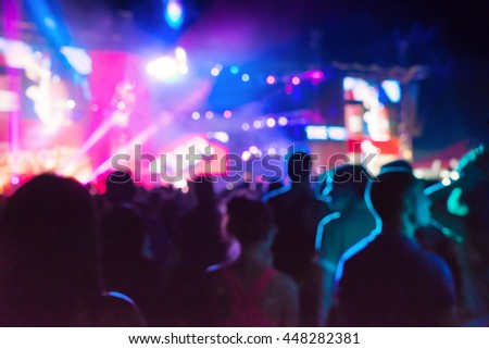 Blurred Youth Music Festival of pop music. Laser show on the stage. The crowd of fans. Bright abstract background ideal for any design. Blurred bokeh basic background for design