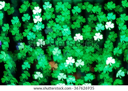 Blurring lights bokeh background of green clovers. Happy Saint Patrick's Day Background - stock photo