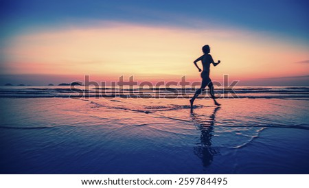Blurring silhouette of running woman on the beach during sunset.