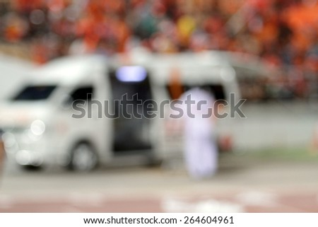 blurry ambulance car stand by at football stadium for help - stock photo