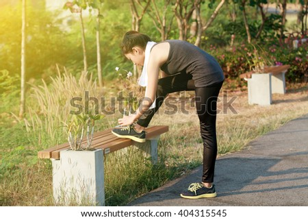 Blurry and soft focus of Athletic woman asia warming up and Young female athlete sitting on an exercising and stretching in a park before Runner outdoor on summer, healthy lifestyle concept