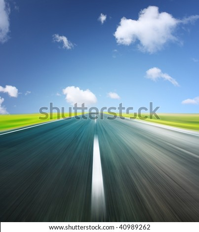 Blurry asphalt road and clear blue sky with clouds - stock photo