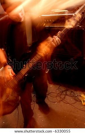 Blurry atmospheric abstract noisy hazy image of a bass player rippin' thru songs. Shot with slow shutter speed and flash for lots of movement and effect. - stock photo