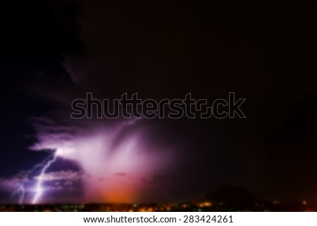 Blurry background with Lightning thunder storm above village - stock photo