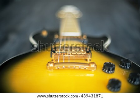 Blurry black and yellow electric guitar. Closeup - stock photo