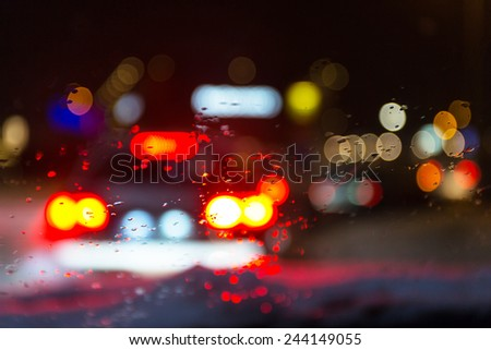 Blurry car silhouette seen through snowy and wet windscreen - stock photo