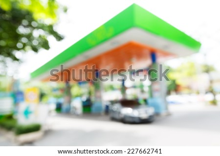 Blurry gas station with car fill up fuel in daytime - stock photo