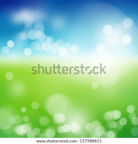 Blurry green field and blue sky with summer sun burst - stock photo