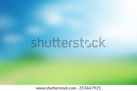 Blurry green field and blue sky with sunshine. - stock photo