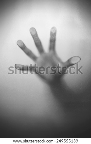 Blurry hand behind matted glass in black and white - stock photo