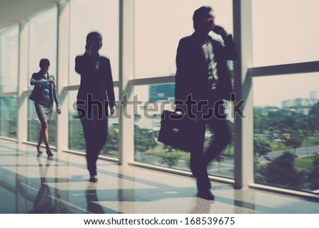 Blurry image of businesspeople being in a hurry indoors - stock photo