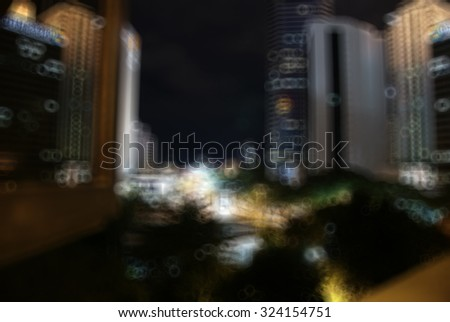 Blurry image of high rise building at night with round bokeh effect. Image suitable for background purpose and contain noise due to high ISO used.
