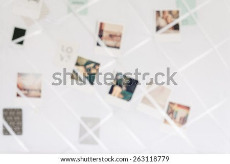 blurry image of polaroids in a white memory board - stock photo