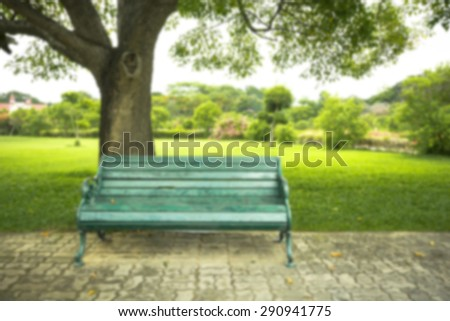 Blurry image.  Old green bench in the park - stock photo