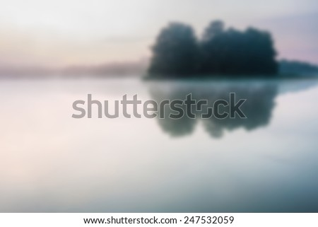 blurry landscape with lake at sunrise useful as background