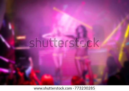 Blurry night club dj party people enjoy of music dancing sound with colorful light. club night light dj party With Smoke Machine and lights. Dark colored background