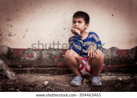 blurry of asian boy sad alone sitting with white bear near old wall cement,vintage tone