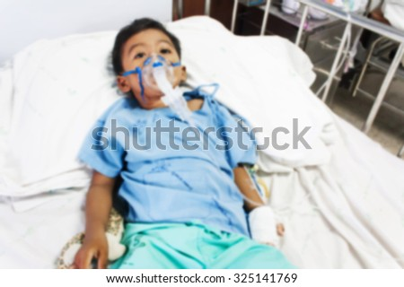 blurry of boy sick in inhaler mask for kid, the hospital - stock photo