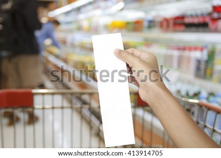 blurry of hand of woman asia checking a bill and a long receipt of supermarket/mall for background and shopping fashion and shopping food,soft focus and selective focus on hand - stock photo