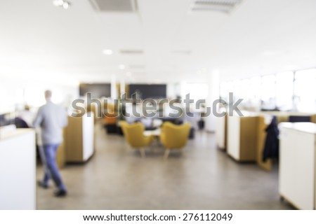 Blurry office with man out of focus walking away, great for use in designs for business or office settings - stock photo