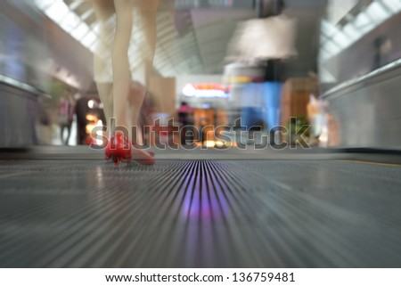 Blurry people waking at airport conveyor belt. Woman's legs in foreground - stock photo
